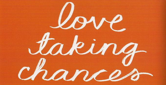 white lettering of love taking chances on orange bakground