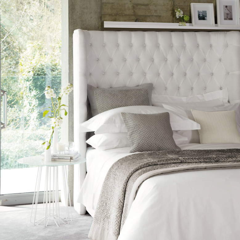 Pillow arrangement on a bed with a high headboard