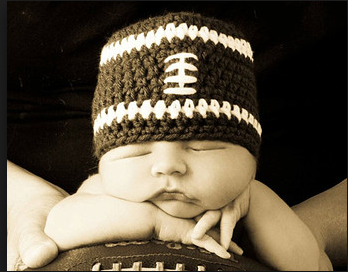 Newborn photo - laying on a football with a football hat