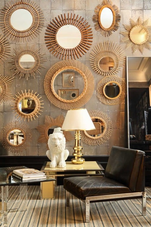 gallery wall of golden starburst mirrors via La Maison Gray - Interiors