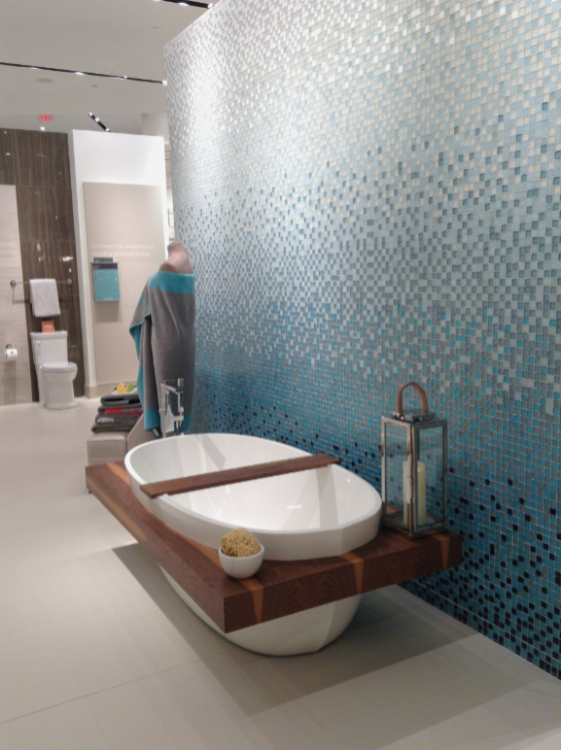 Pitch bathroom showroom photo with tiled walls and beautiful bath
