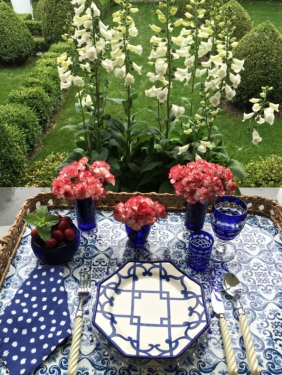 Red flowers with blue and white china for Fourth of July Decorations