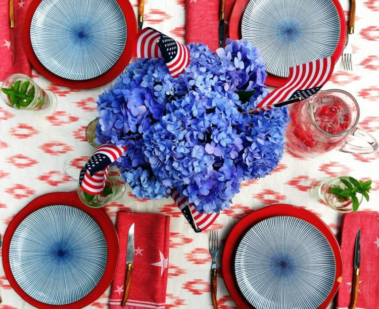 Vibrant blue hydrangeas with American Flags for a centerpiece for 4th of July Decoration Photo