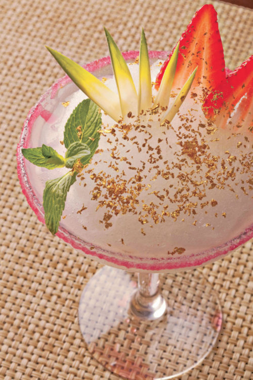 Frozen cocktail with edible gold flakes spread around photo