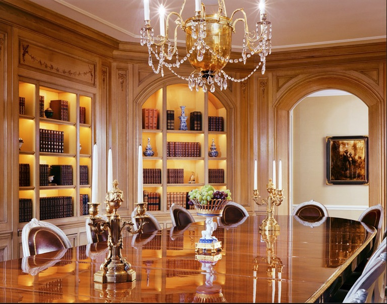 Photograph of a luxurious book lined traditional dining room by Michael Simon of New York City.